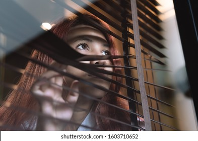 Asian woman looking through window blinds spying on neighbours - Young lonely millennial woman peeping through glass observing gossip and action outdoors - introvert, privacy and intrusive concepts