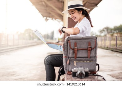 Asian woman looking watch at the train station on holiday. with hat, backpack and map.