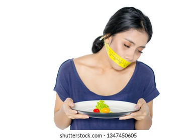 Asian woman looks unhealthy while holding a plate of salad and covering her mouth with a measure tape in the studio