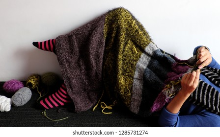 Asian woman lying on floor of home to knit woolen blanket for warm in wintertime, knitting is hobby in leisure activity to make handmade gift, photo of woman hand working from front view on day