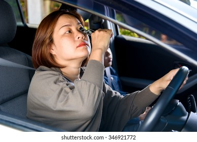 Asian woman make up during driving. Road safety concept.
