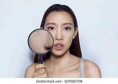 Asian woman with makeup on, holding magnifying glass to show bumpy skin  (clog pores), which appears when using pour coverage foundation, tainted face skin.
