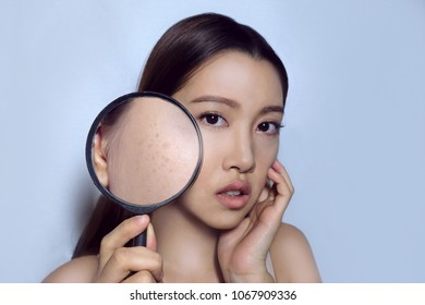 Asian woman with makeup on, using magnifying glass to show dark spot (Seborrheic keratosis), which appears when using bad coverage, too much exposing to the sun.