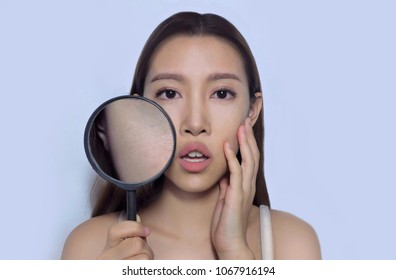 Asian woman with makeup on, using magnifying glass to show bumpy skin  (clog pores), which appears when using pour coverage foundation, tainted face skin.