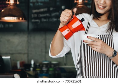 Asian woman making coffee in cafe