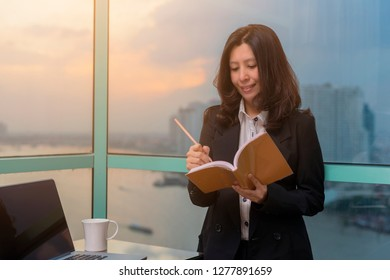 Asian woman making notes in book and using Laptop in office.