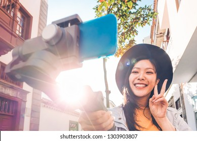 Asian woman making video blog with smartphone gimbal outdoor - Happy Asiatic influencer having fun with new technology trends for social media - People, generation z, tech and youth lifestyle concept