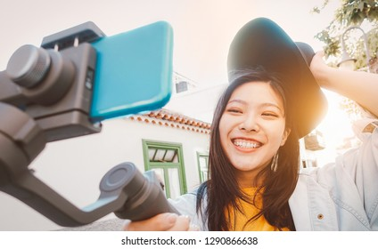 Asian woman making video with smartphone gimbal outdoor - Happy Asiatic girl having fun with new technology trends for social media - Millennials people, generation z, tech and youth lifestyle concept