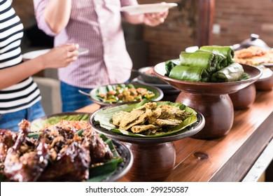Asian woman and man choosing food at Indonesian buffet in restaurant