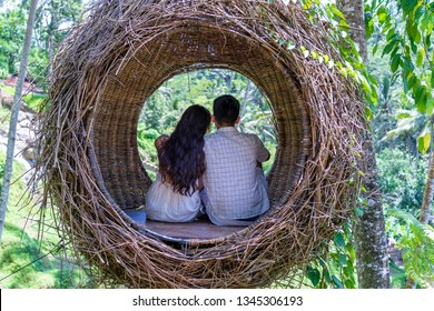 Asian woman and man enjoying his time sitting on a bird nest in the tropical jungle near the rice terraces in island Bali, Indonesia . Nature and travel concept
