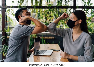 Asian woman and man friends wearing face mask outdoors. Friends greeting and shaking with elbows as new normal. Corona Virus - Covid 19 elbow bumps greeting style to prevent contact and virus spread.