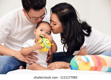 Asian woman and man kissing their baby with love on bed.Mother and Father with lovely son.Happy family concept in house.Love and relationship idea.Warmness and happiness.Parent with little boy.