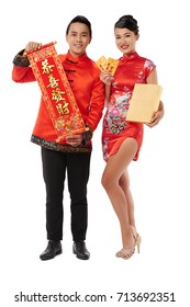 Asian woman and man in traditional clothes showing attributes of Chinese New Year