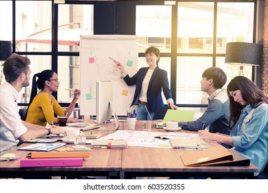 Asian woman management director in casual suit  explaining internal meeting to her project team in modern office. The multi ethnic business person group. Project and Business concept.