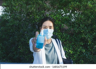 Asian woman with mask alcohol bottle in her hand ready to spray outside her house