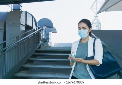 asian woman with mask going to work spray her hand with alcohol to kill virus covid19