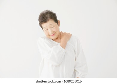 Asian woman massages the senior citizen's shoulders