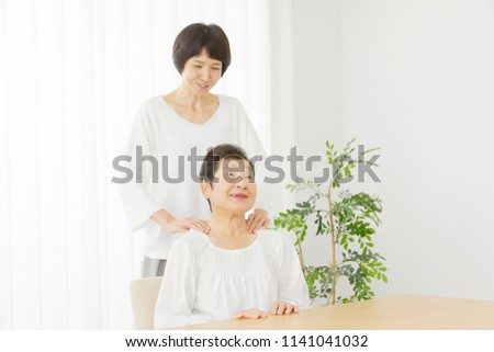 Asian Woman Massages The Senior Citizens Shoulders