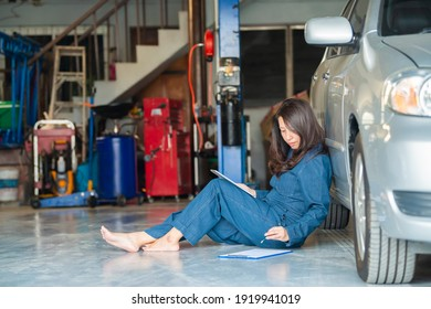 Asian woman mechanic using tablet to fix car and writing to a clipboard while sitting on the floor at the repair garage. Copy space