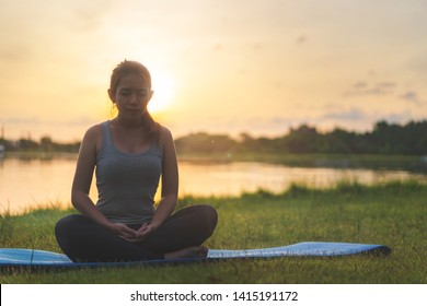 Asian woman meditating and sit in the lotus pose at park, Healthy and Yoga Concept,Mind-body improvements concept, Selective focus, Copy space.