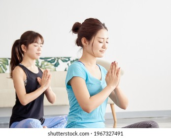 Asian woman meditating with yoga - Shutterstock ID 1967327491
