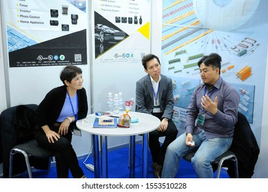 Asian woman and men, businessmen, sitting at the negotiating table and communicating. Exhibition Industrial Ukraine-2019. November 6, 2019.Kiev, Ukraine