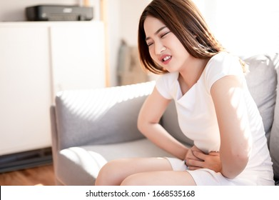 Asian a woman with menstrual cramps, stomachache torture. Healthy, pharmacy, self care concept.