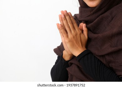 Asian woman in Muslim dress stands up in a greeting pose to Namaste hands, welcoming guests, Eid Fitr greeting. Isolated on white background
