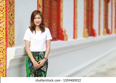 Asian woman in native southern Thai style pattern paint pants in with traditional Thailand Buddhist temple architecture.