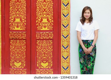 Asian woman in native Thai style pattern paint pants in with traditional Thailand Buddhist temple architecture.