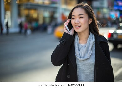 Asian woman in New York City Times Square calling talking on phone callephohe
