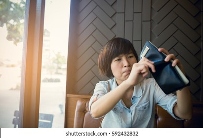 Asian woman with no money in coffee shop she looking empty pocket. money No money Concept.
