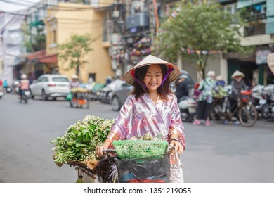 Asian woman in a non la hat walks down the street with a bicycle laden with jasmine flowers. She smiles and looks ahead.