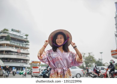 Asian woman in a non la hat posing against a busy street. Behind her road traffic, cars, passers-by and motorcyclists. A girl holds a hat with two hands and looks away with a smile