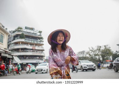 Asian woman in a non la hat posing against a busy street. Behind her road traffic, cars, passers-by and motorcyclists. The girl laughs, holding the dress from the wind