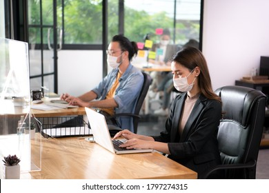 Asian woman office worker wearing face mask working in the new normal office and doing social distancing during coronavirus COVID-19 pandemic