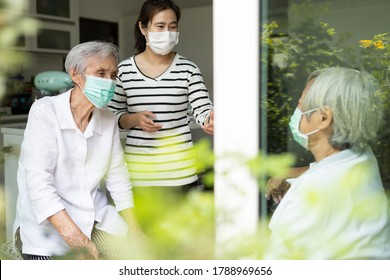 Asian woman and old elderly with medical masks on the face,daughter talking happily visited her senior mother at home,wear a protective face mask for safety while close to each other,New normal life