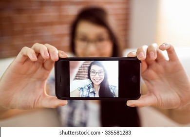 Asian woman on the couch taking selfie at home in the living room