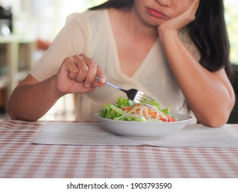 Asian woman on diet time, she dislike to eat vegetables salad on the plate.