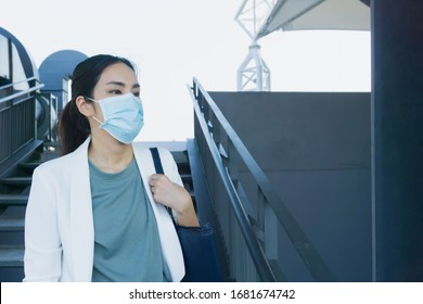 Asian woman on trian station going to work with mask to protect virus
