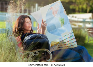 Asian woman on vacation with map, backpack relaxing outdoor with leave space for adding your content.
