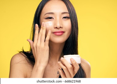 Asian, woman on yellow background applies cosmetic face cream.