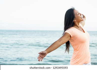 Asian woman with open arms on the beach.