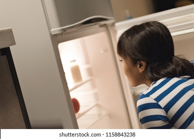 Asian woman open a refrigerator at home