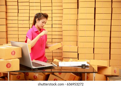 Asian woman packing boxes among stack of parcels in her shopping online business at home with laptop computer on desk