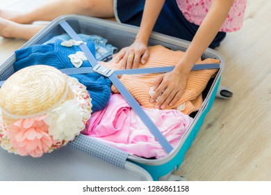 Asian woman packing a luggage on wooden floor