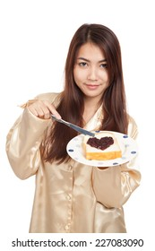 Asian woman in pajamas with bread and heart shape berry jam  isolated on white background