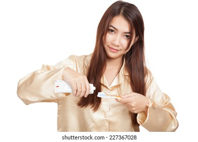 Asian woman in pajamas smile with toothbrush and toothpaste  isolated on white background