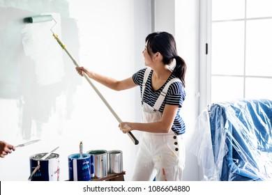 Asian woman panting house wall