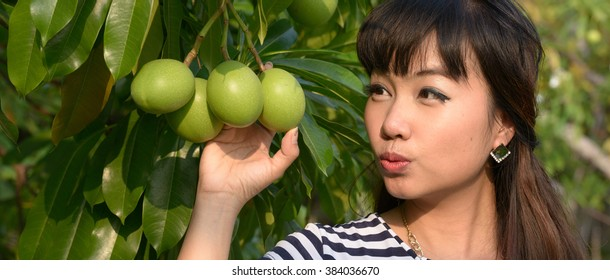 Asian woman in park holding fruit